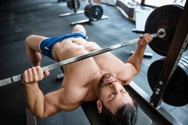 フィットネス ジムでベンチプレスをしているハンサムな筋肉の男の肖像