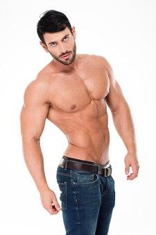 Портрет красивого мускулистого мужчины с обнаженным торсом, позирующего изолированно на белой стене
