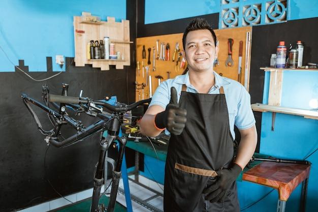 Портрет красивого ремонтника с пальцами вверх в фартуке