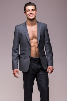 Портрет красивого сексуального мужчины в куртке и с обнаженным торсом, изолированного на белой стене