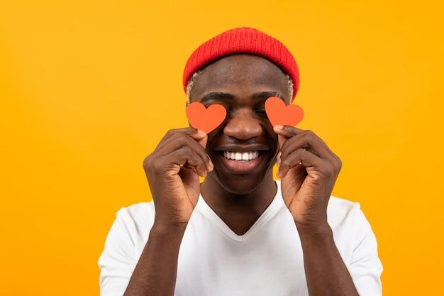노란색 배경에 발렌타인 데이에 대한 두 개의 작은 눈 모양의 엽서를 들고 흰색 티셔츠에 잘 생긴 웃는 미국의 어두운 피부 남자의 초상화