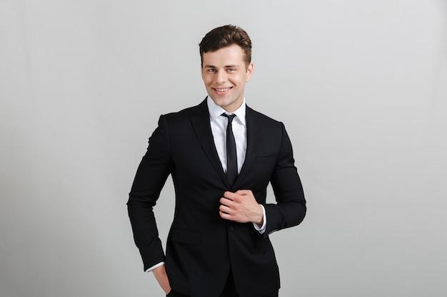 Портрет красивого улыбающегося бизнесмена в костюме постоянного изолированного