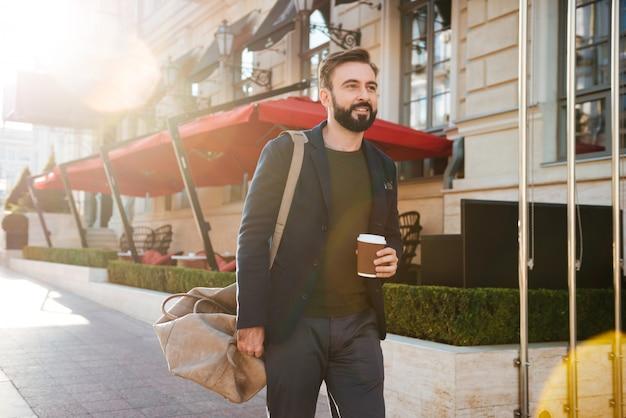 커피를 마시는 잘 생긴 웃는 남자의 초상
