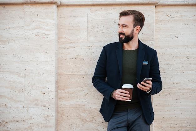 Портрет красивый улыбающийся мужчина держит чашку кофе