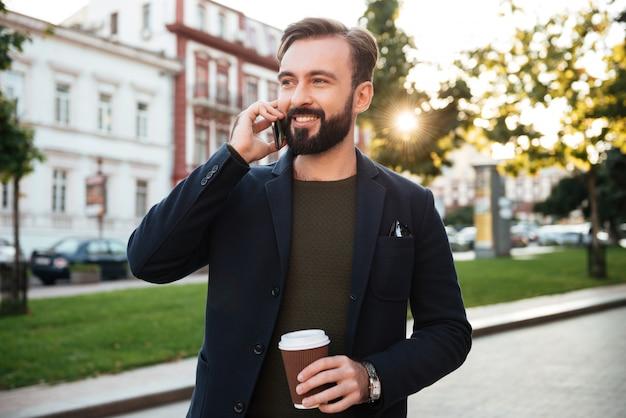 휴대 전화에 잘 생긴 웃는 남자의 초상