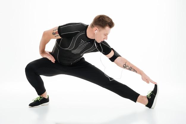 ジョギングの前にストレッチ体操をしているハンサムなスポーツマンの肖像画
