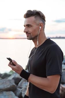 Портрет красивого спортсмена, слушающего музыку