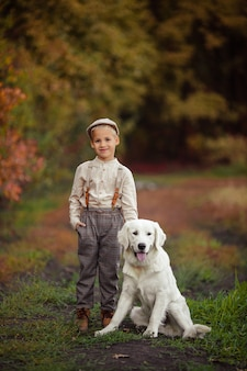 ペットのレトリーバーと帽子のハンサムなスタイリッシュな男の子の肖像画
