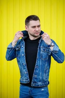 Портрет красивого стильного парня, человека в черной пустой футболке, стоящего на желтом фоне стены. городской стиль в одежде, современный модный образ. мужская мода