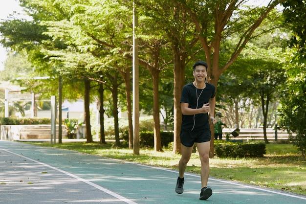Портрет красивого молодого спортсмена азиатского парня, бегающего под тренировочную музыку