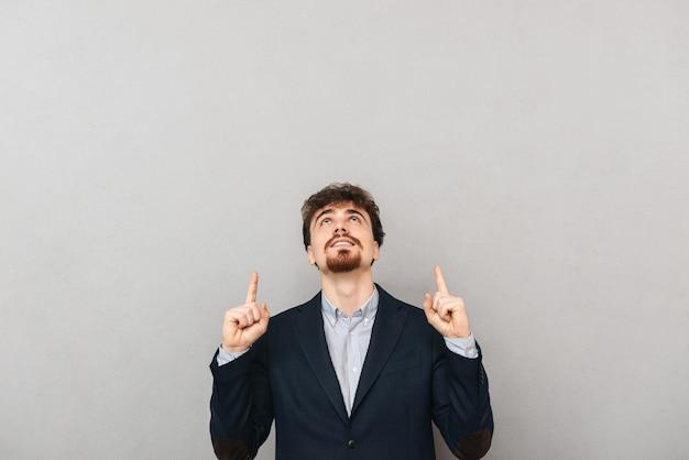 회색 벽 가리키는 위에 절연 잘 생긴 젊은 비즈니스 남자의 초상화.