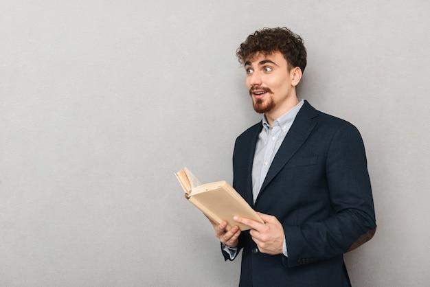 책을 읽고 회색 벽 위에 절연 잘 생긴 젊은 비즈니스 남자의 초상화.