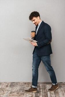 커피를 마시는 신문을 읽는 회색 벽 위에 절연 잘 생긴 젊은 비즈니스 남자의 초상화.