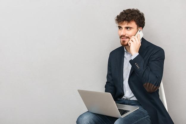 커피로 마시는 랩톱 컴퓨터를 사용하여 회색 벽 위에 절연 잘 생긴 젊은 비즈니스 남자의 초상화.