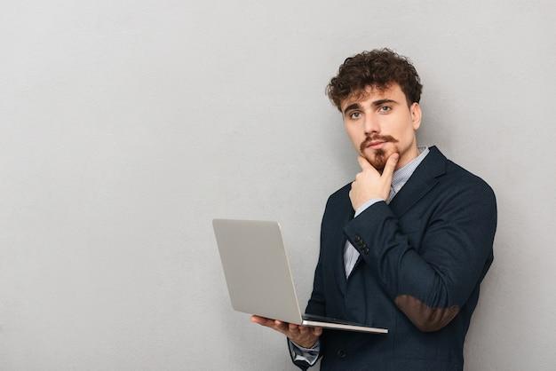 랩톱 컴퓨터를 사용하는 회색 벽 위에 절연 잘 생긴 젊은 비즈니스 남자의 초상화.