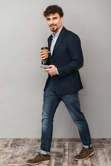 커피를 마시는 휴대 전화를 사용 하여 회색 벽에 고립 된 잘 생긴 젊은 비즈니스 남자의 초상화.