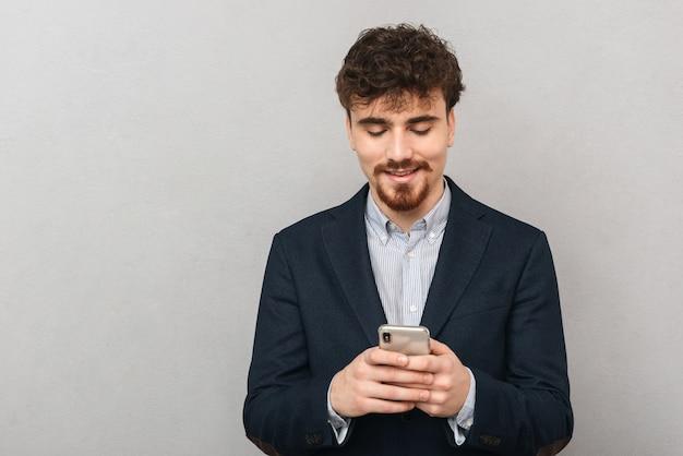 휴대 전화를 사용 하여 회색 벽 위에 절연 잘 생긴 젊은 비즈니스 남자의 초상화.