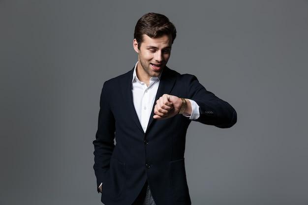 회색 벽 위에 절연 양복을 입고 잘 생긴 젊은 사업가의 초상화, 그의 손목 시계를보고