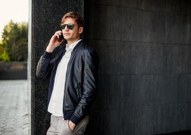 검은 선글라스와 가죽 재킷을 입은 잘생긴 젊은 사업가의 초상화가 밖에서 휴대전화로 통화하고 있습니다.