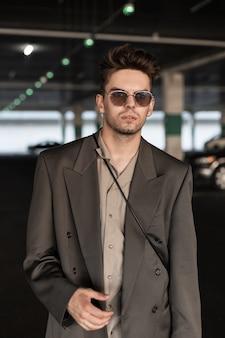 ファッショナブルなジャケットとシャツのサングラスと街を歩くハンサムな青年実業家モデルの肖像画