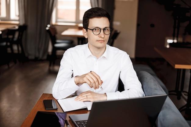 カメラを見ながら彼の手でペンで作業しているコーヒーショップの机に座っているハンサムな青年実業家の肖像画。