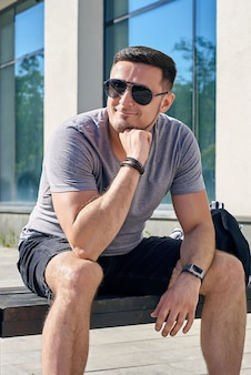 건물 근처 벤치에 앉아 웃고 있는 선글라스를 끼고 검은 머리를 한 잘생긴 백인 남자의 초상화