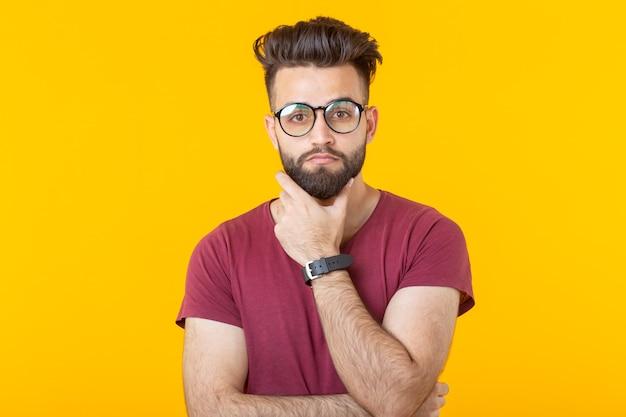 眼鏡をかけ、思慮深く見ているひげを持つハンサムな若い男性のヒップスターの肖像画