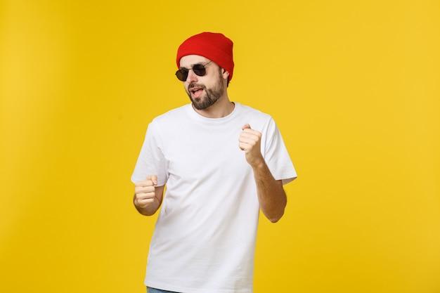 Портрет красивого молодого человека, танцующего и слушающего музыку, изолированного на желтом.