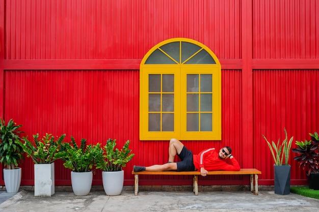 빨간 재킷과 노란 창과 화분에 심은 식물이있는 빨간 건물에 대해 포즈를 취하는 검은 반바지를 입은 잘 생긴 젊은 남자의 초상