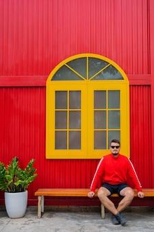 노란색 창과 화분에 심은 꽃이있는 빨간색 건물의 배경에 대해 포즈를 취하는 빨간 재킷과 검은 색 반바지를 입은 잘 생긴 젊은 남자의 초상