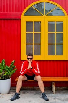 Портрет красивого молодого человека в красном пиджаке и черных шортах позирует на фоне красного здания с желтым окном и цветами в горшках