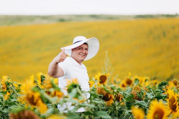 ひまわり畑で白人女性の帽子でハンサムな若い男の肖像画。男は屋外で楽しんでいます。コピースペース。セレクティブフォーカス