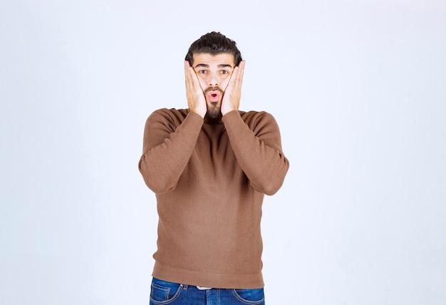 Портрет красивого молодого человека в повседневном свитере, держащего ладони возле щек.