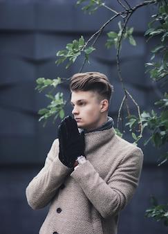 街の通りに立っている手袋でハンサムな若い男の肖像
