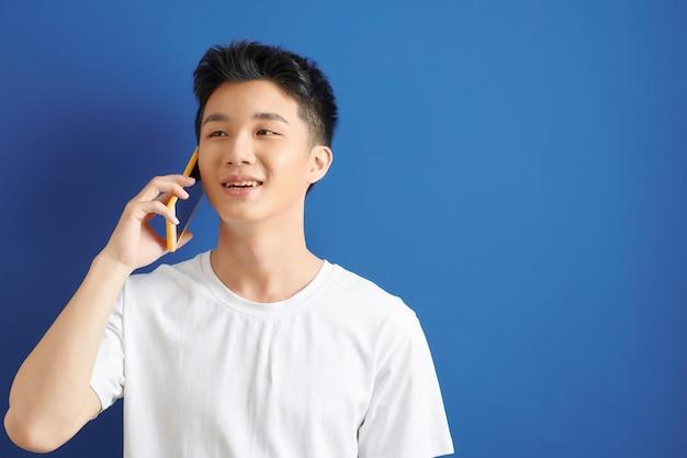 青い背景で隔離の携帯電話で話している白いtシャツのハンサムな若い男の肖像画