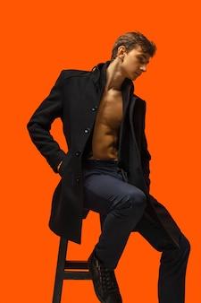 Портрет красивого молодого человека на оранжевой стене