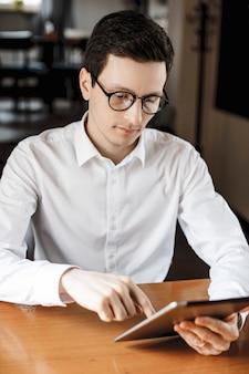 眼鏡をかけている白いシャツのデスクドレッサーに座っている間タブレットを使用してハンサムな若い男の肖像画。