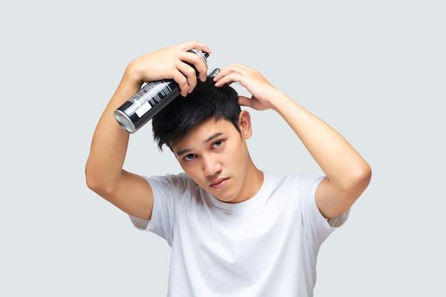 ヘアスプレーで髪をスタイリングする彼の手を使用してハンサムな若い男の肖像画