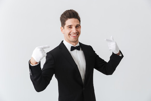 Портрет официанта красивого молодого человека в смокинге и перчатках, стоящего изолированно над белой стеной, указывая на себя