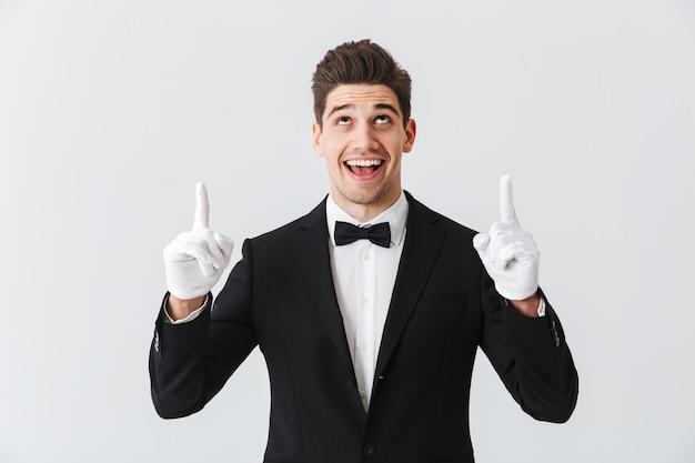 Портрет официанта красивого молодого человека в смокинге и перчатках, стоящего изолированно над белой стеной, указывая пальцами на пространство для копирования