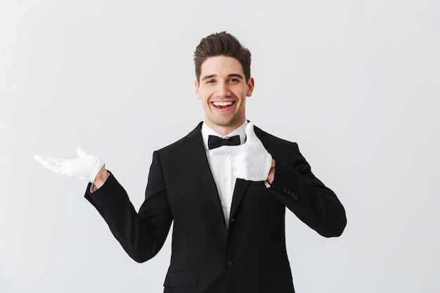 Портрет официанта красивого молодого человека в смокинге и перчатках, стоящего изолированно над белой стеной, представляя пространство для копирования