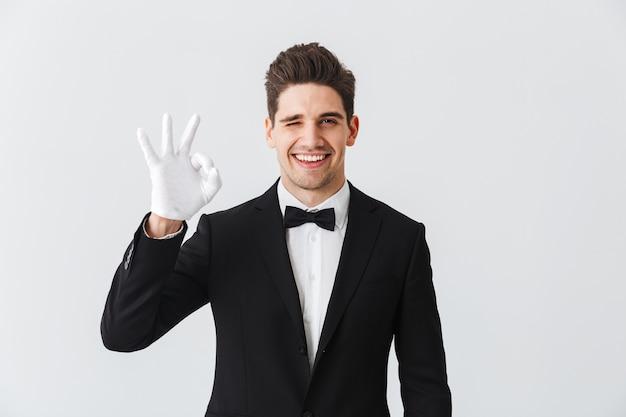 Портрет официанта красивого молодого человека в смокинге и перчатках, стоящего изолированно над белой стеной, показывая хорошо