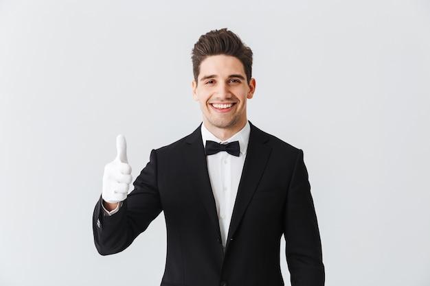 Портрет официанта красивого молодого человека в смокинге и перчатках, стоящего изолированно над белой стеной, показывая большие пальцы руки вверх