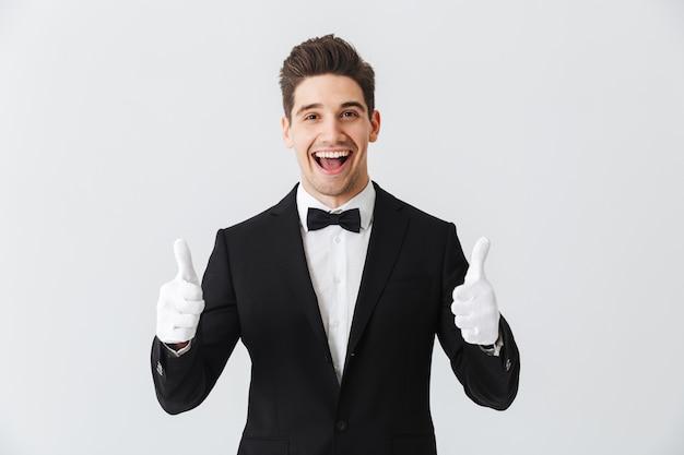 Портрет официанта красивого молодого человека в смокинге и перчатках, стоящего изолированно над белой стеной