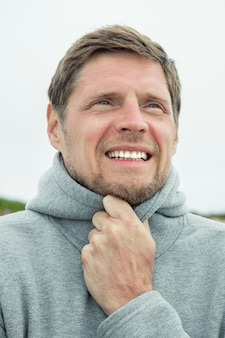 Портрет красивого молодого человека, идущего вдоль океана вечером путешествующие люди концепции