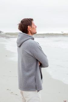 夕方に海に沿って灰色のパーカーを歩いているハンサムな若い男の肖像画