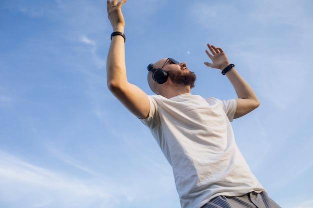 曇り空のバックに対してヘッドフォンで音楽を聞いているひげを持つハンサムな若い男の肖像...