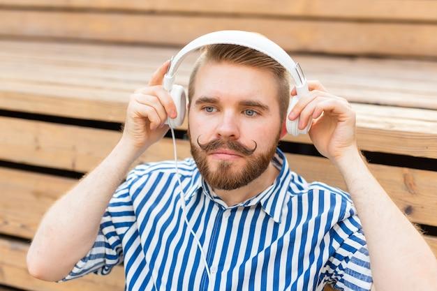 Портрет красивого молодого студента с усами и бородой, расслабляющегося в парке с