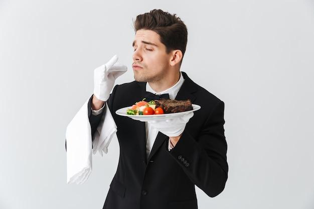 白い壁の上のプレートにビーフステーキ料理を示すタキシードのハンサムな若いウェイターの肖像画