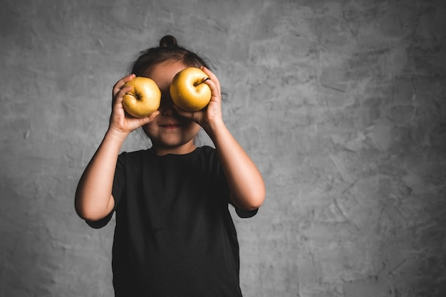 Портрет маленькой девочки счастья есть зеленое яблоко на сером фоне. здоровье, здоровая еда